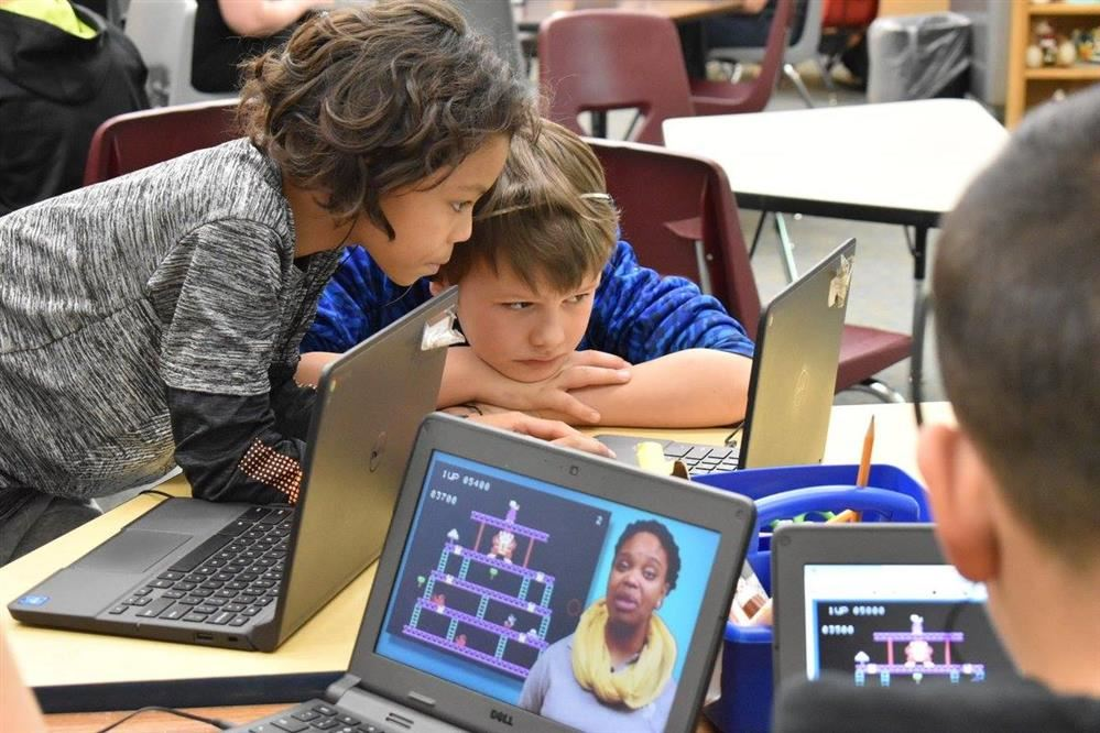 elementary kids working together on chromebooks in classroom