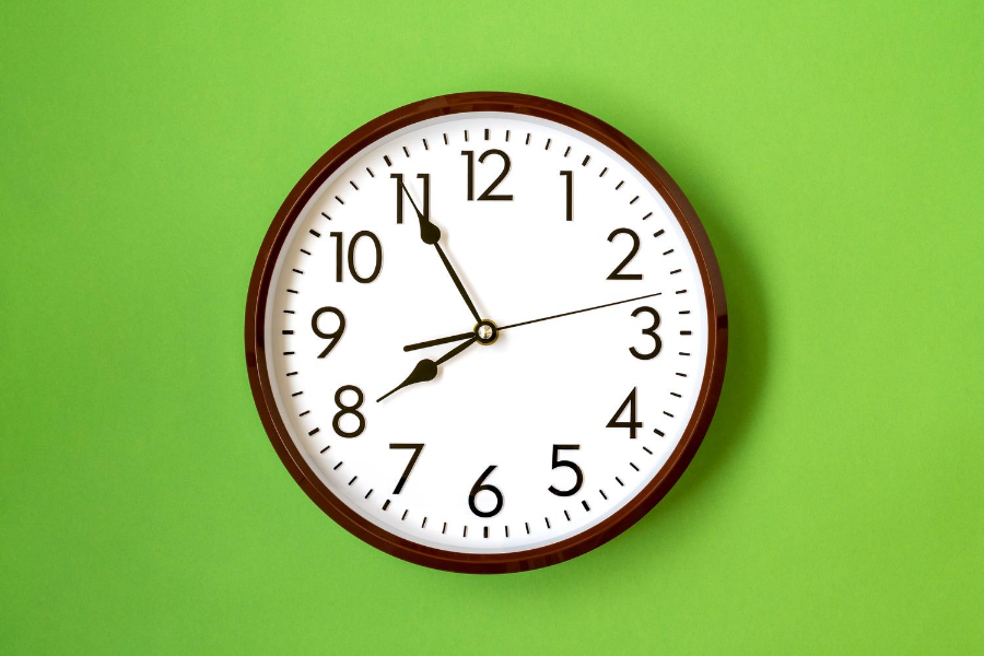 School wall clock on a neon green background