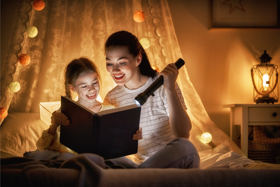 Mom holding flashlight reading to daughter in a tent